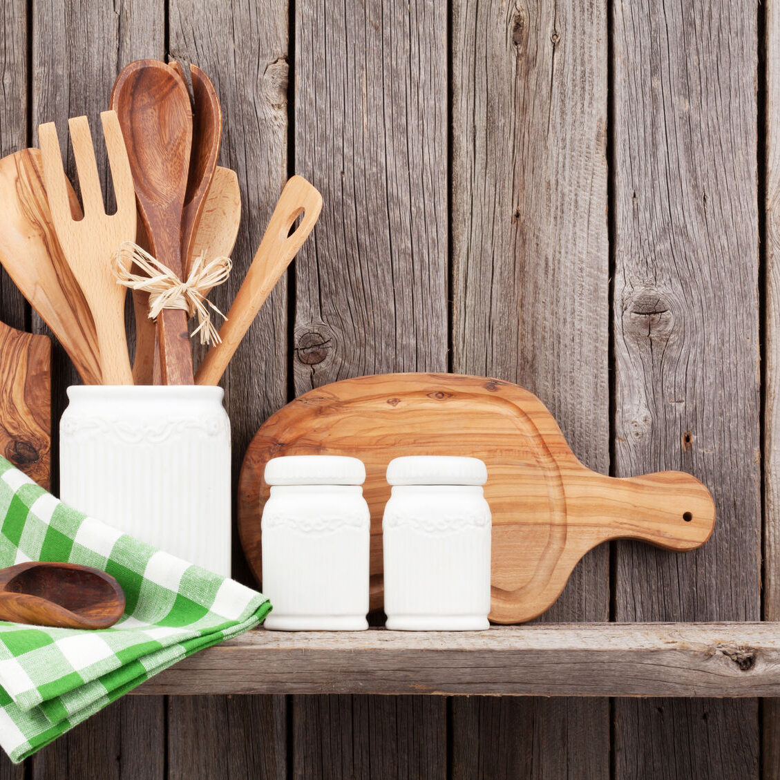 48499900 - kitchen cooking utensils on shelf against rustic wooden wall
